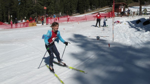 Clara skiing the obstacle course and Alex making shots in the background.